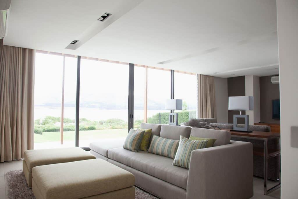 A huge luxurious modern living room with gray square arms, sofas beige curtain, and a huge window on the side