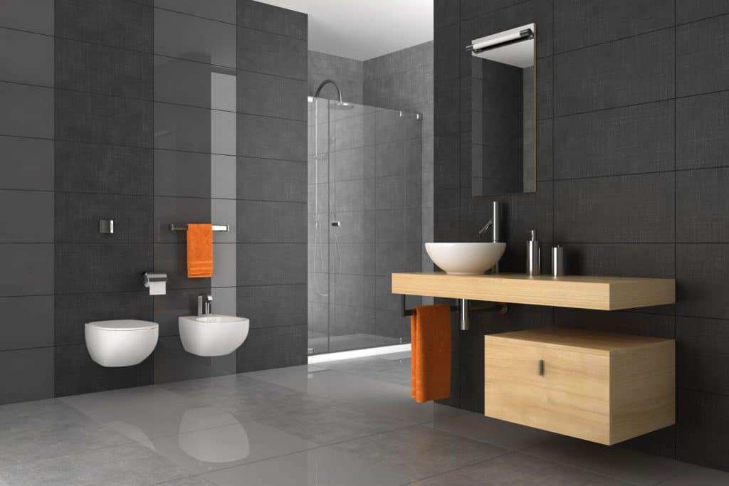 A minimalist themed bathroom with gray walls, white bathroom lavatory and toilet, and orange towels