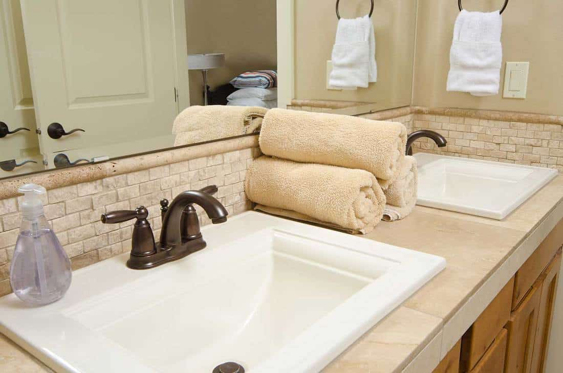 A modern bathroom sink with rolled up towels and hand soap
