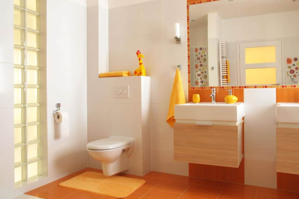 A modern bathroom with white painted walls and a decorative orange tiled wall on the vanity