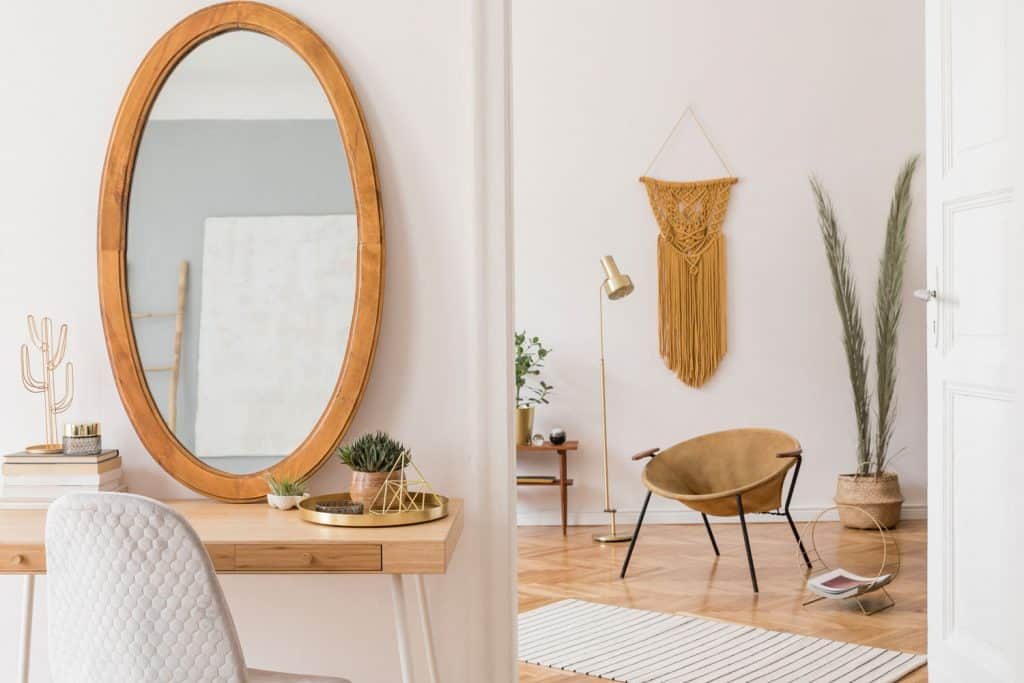 A modern retro themed dressing room with a round wooden framed mirror, solid wooden table, and white painted walls