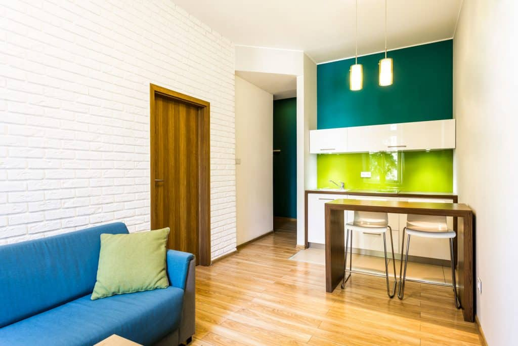 A modern small living room with a green accent wall on the kitchen section and a white brick decorative wall