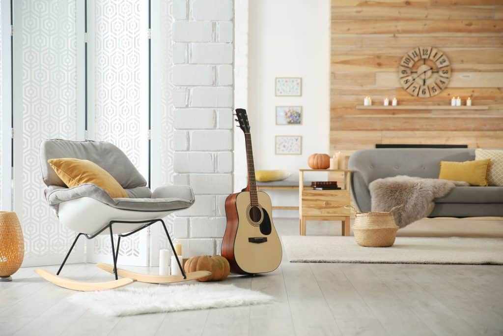 A rustic themed living room nook with a gray chair, orange pillows, gray flooring, and a guitar on the wall