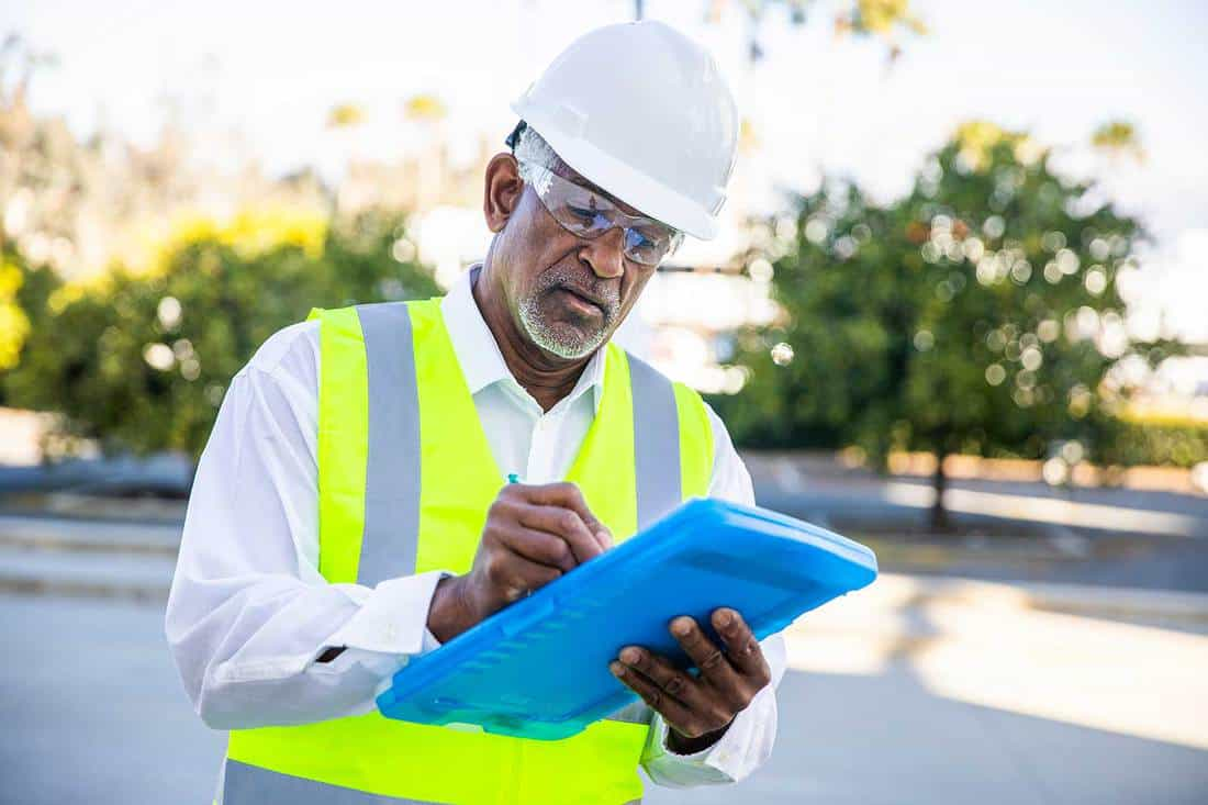 A senior black male construction site manager visually inspects a building project