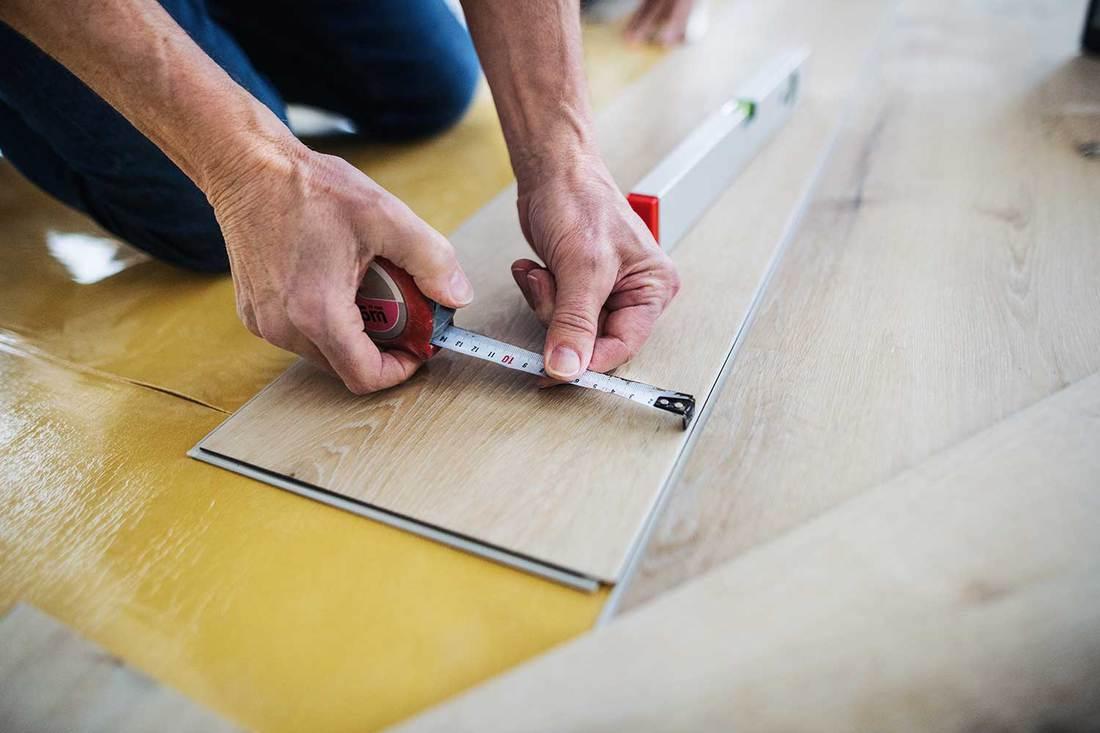 A senior man laying and measuring vinyl flooring