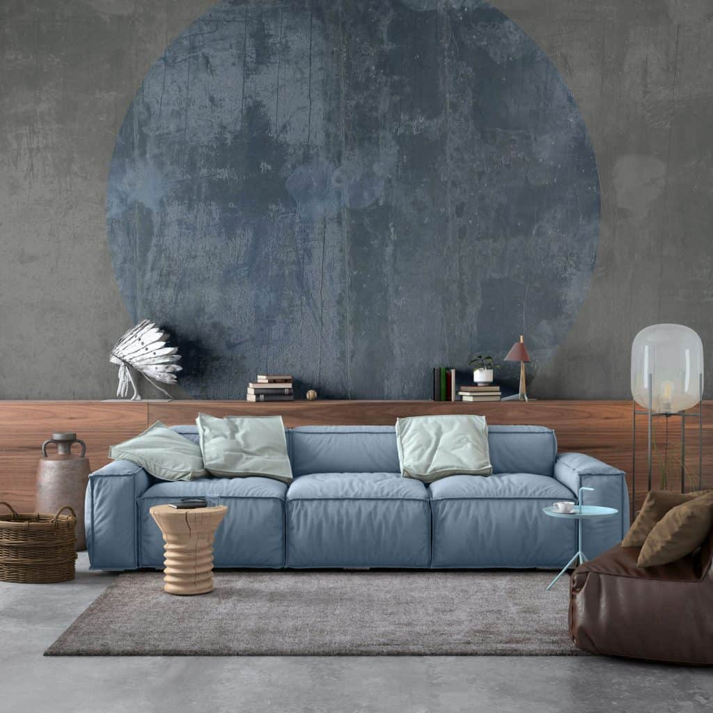 A simple rustic themed living room with a blue long sleeper sofa and a gray carpet in front