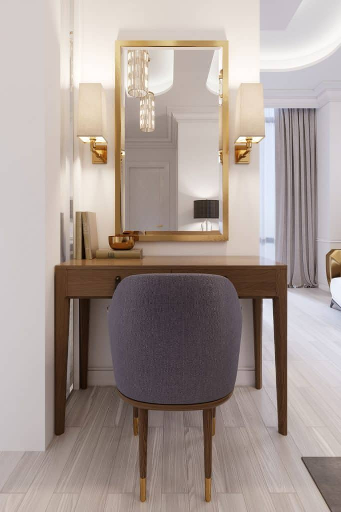 A small dressing area with a wooden dressing table, a wooden framed mirror, and lamps on the sides