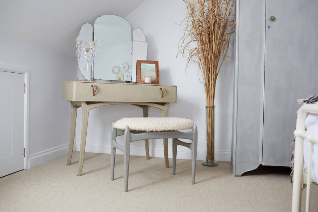 A small dressing table with vintage curved mirrors, small gray chairs, and a decorative withered plant