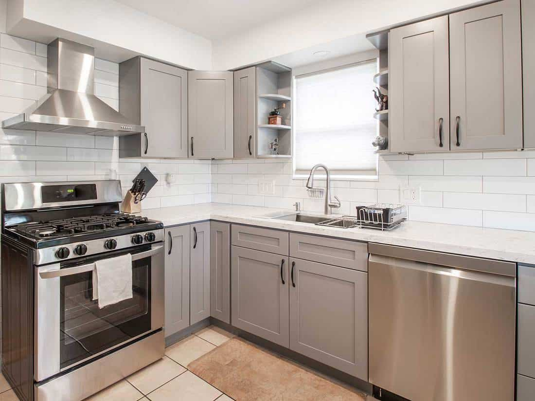 A small modern kitchen with gray cabinets and stainless steel appliances