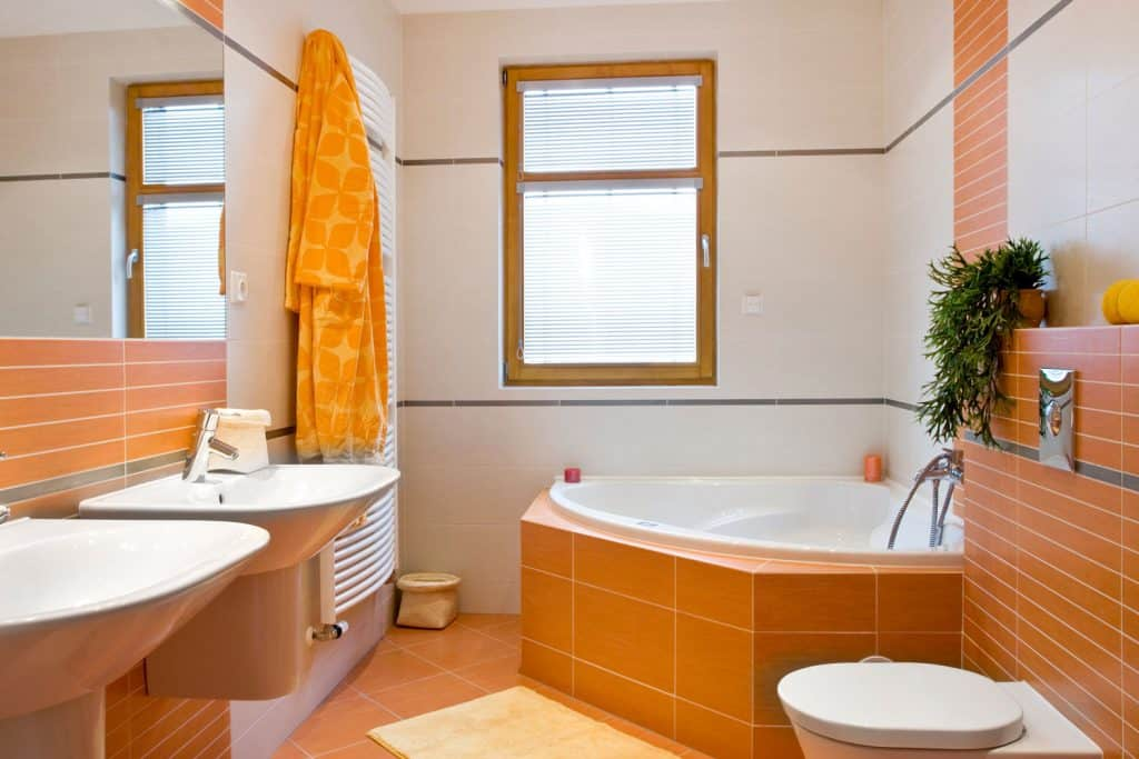 A small narrow bathroom with orange tiled walls and a white wall on the window section