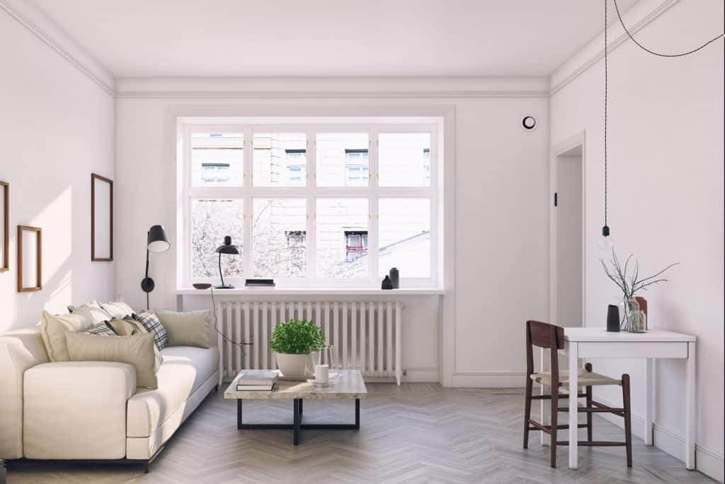 A small narrow living room with white furniture's, indoor plants, and picture frames on the wall