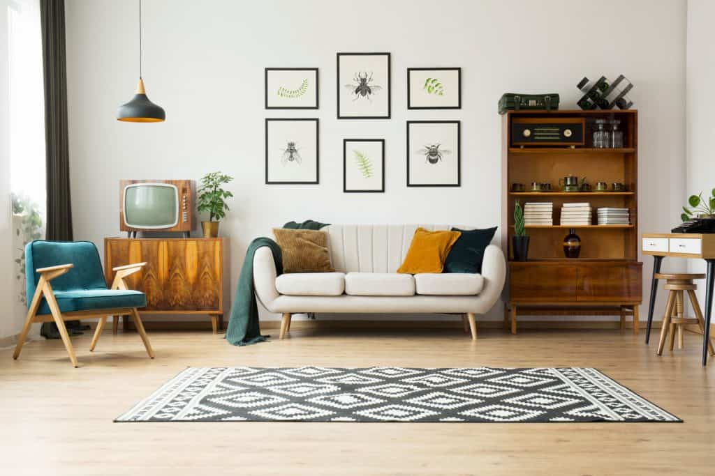 A spacious and elegant living room with a white wall, picture frames on the wall, wooden furniture's, and a patterned carpet