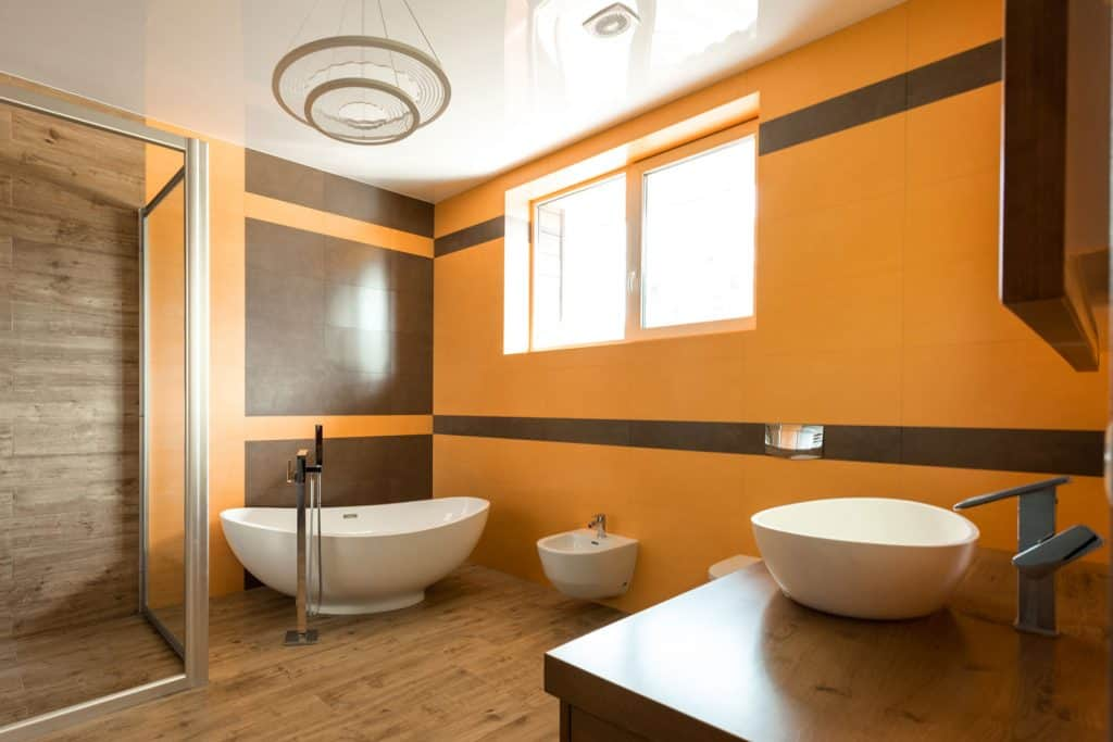 A spacious and orange walled bathroom with a glass wall shower area, white bathtub and wooden vanity area