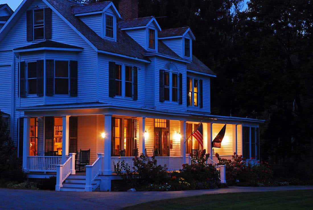 A suburban home with lights on at dusk