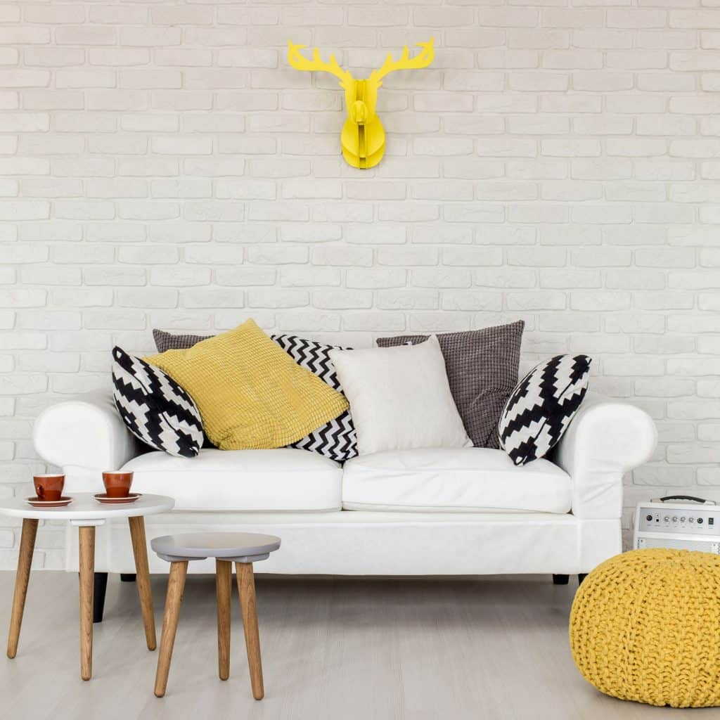 A white small loveseat sofa with patterned throw pillows and round coffee tables