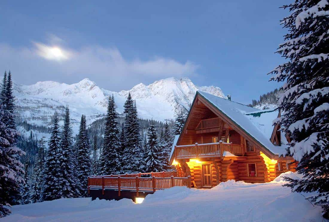 A winter scenic of a rustic, timber-framed lodge