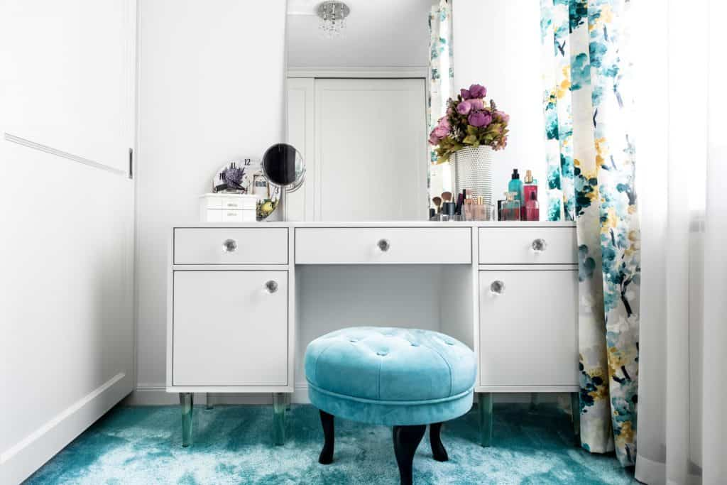 A women's dresser table with a blue ottoman chair, white cabinet dresser, and flowers on top