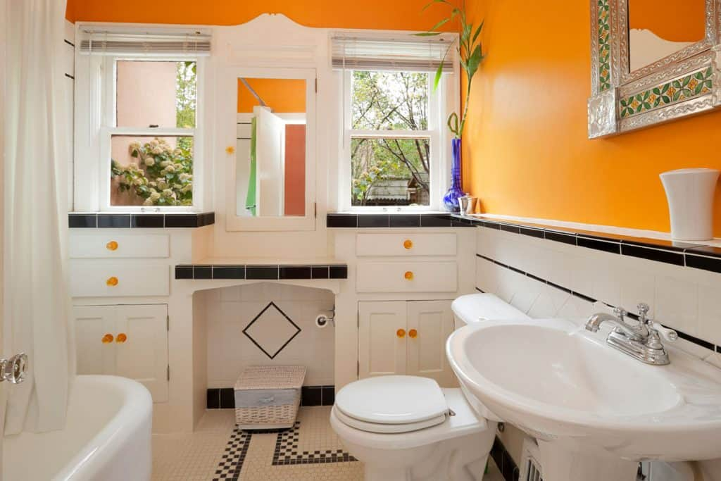 An orange wall bathroom with white paneled cabinets, white tiled base wall, and a white bathtub and white shower curtains