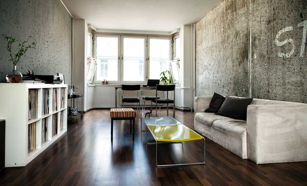 Apartment living room interior with parquet floor, sofa and study table and chairs