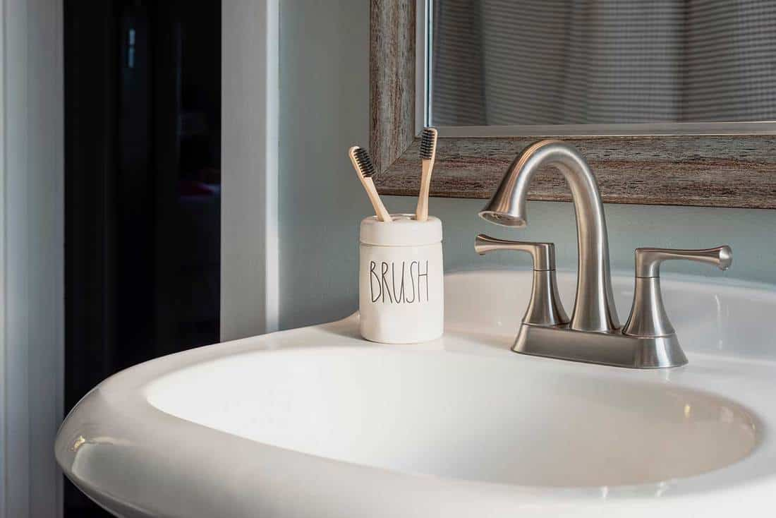 Bamboo toothbrushes in a ceramic holder on bathroom sink