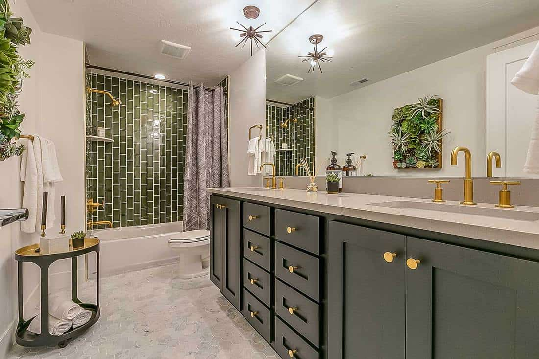 Beautiful green theme bathroom with brass faucets and fixtures