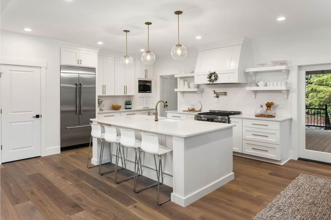 Beautiful kitchen in new luxury home with island, pendant lights, and hardwood floors. sink in the kitchen island