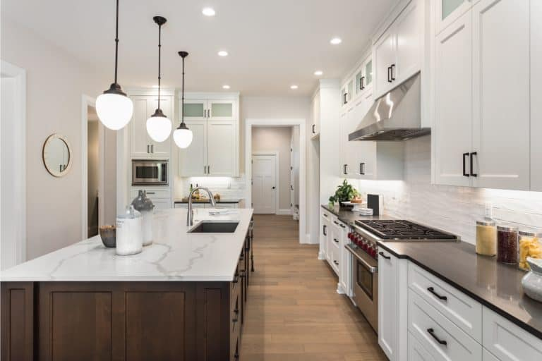 Beautiful kitchen in new luxury home with island, pendant lights, and white cabinets. What Color Floor With White Cabinets