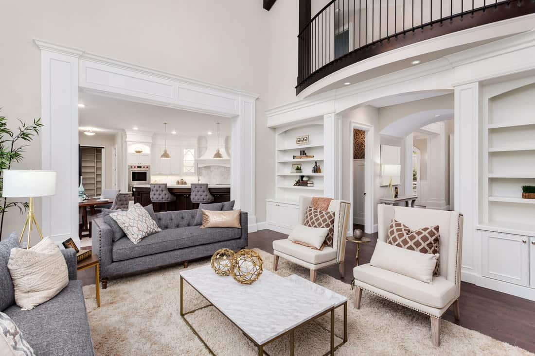 Beautiful living room interior with tall vaulted ceiling, loft area, hardwood floors and fireplace in new luxury home