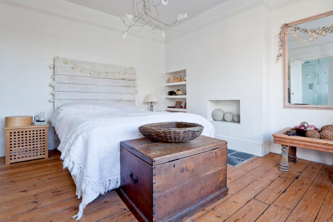 Bedroom interior with exposed wooded floor and furnishings including white painted walls