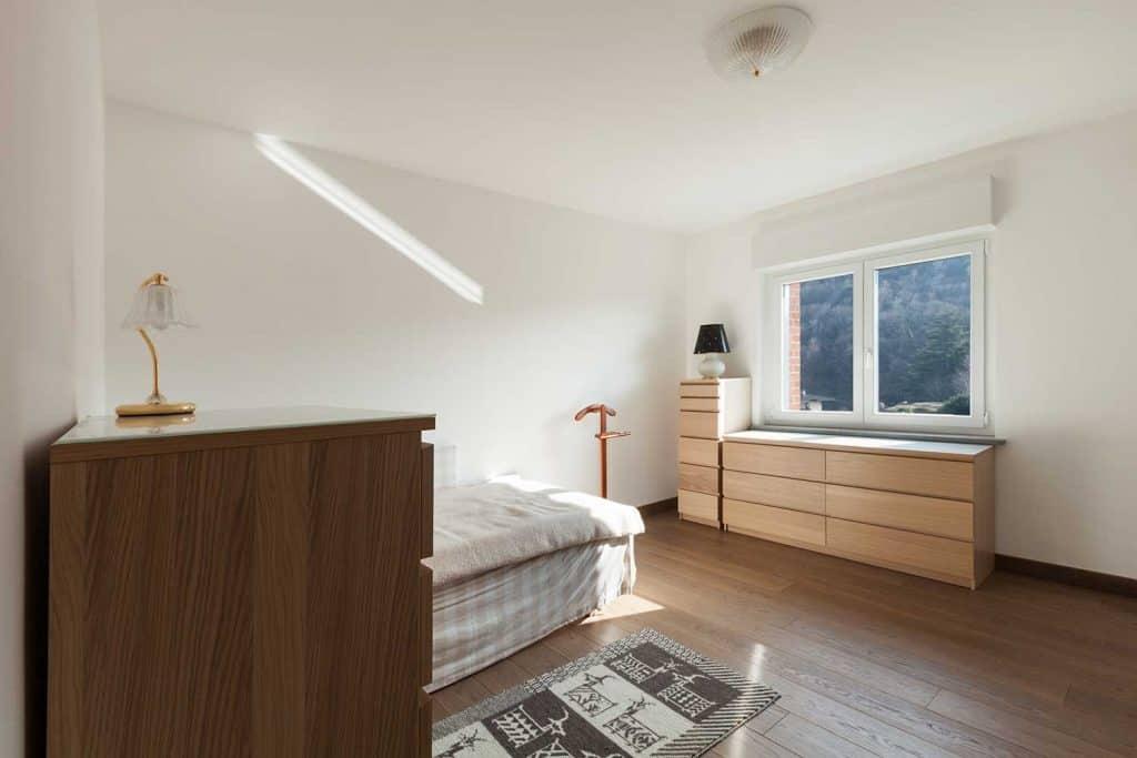 Bedroom interior with wooden cupboard under the window