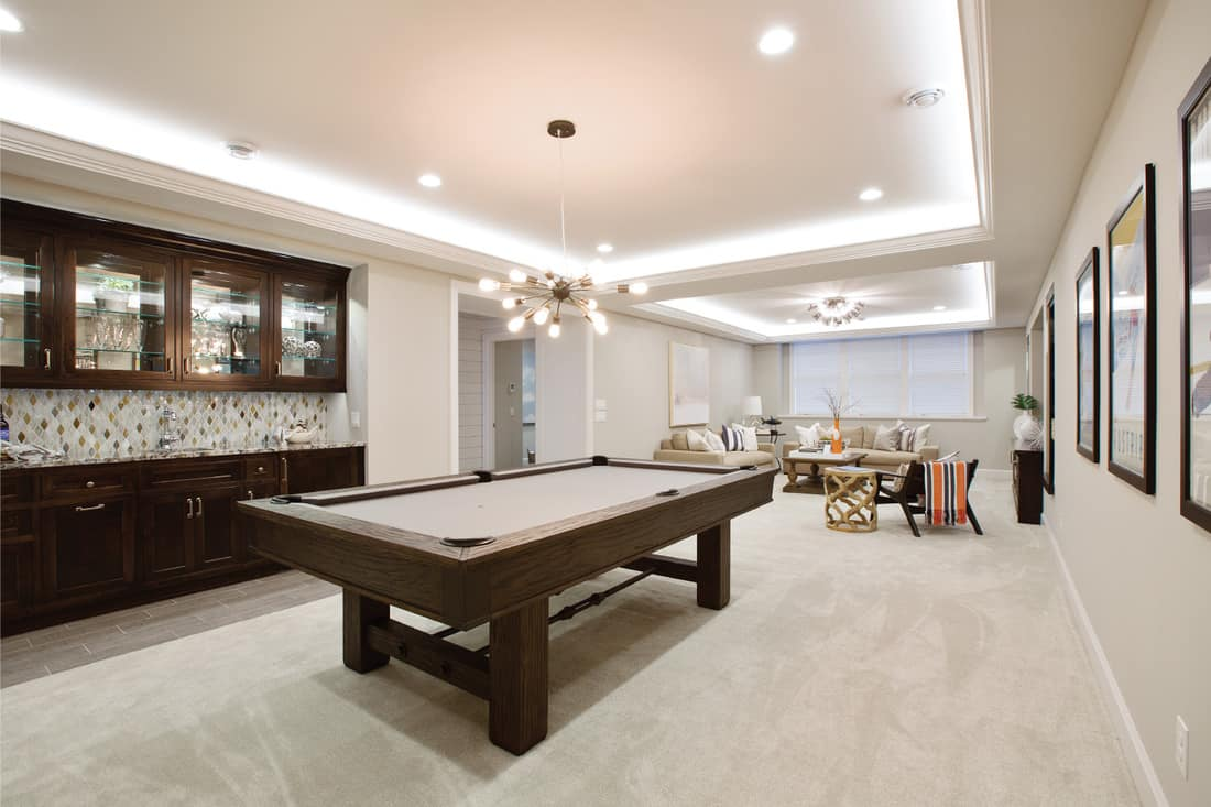 Billiards table with kitchenette nearby for everything you need in the basement