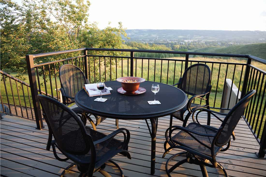 Black Wrought Iron patio furniture. Glass of red and glass of white white on table. Quiet and peaceful spot with rolling hills. powder coated metal railing