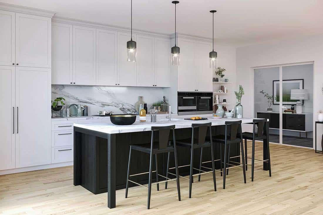 Black and white kitchen island, white cabinets and parquet flooring in a modern kitchen interior
