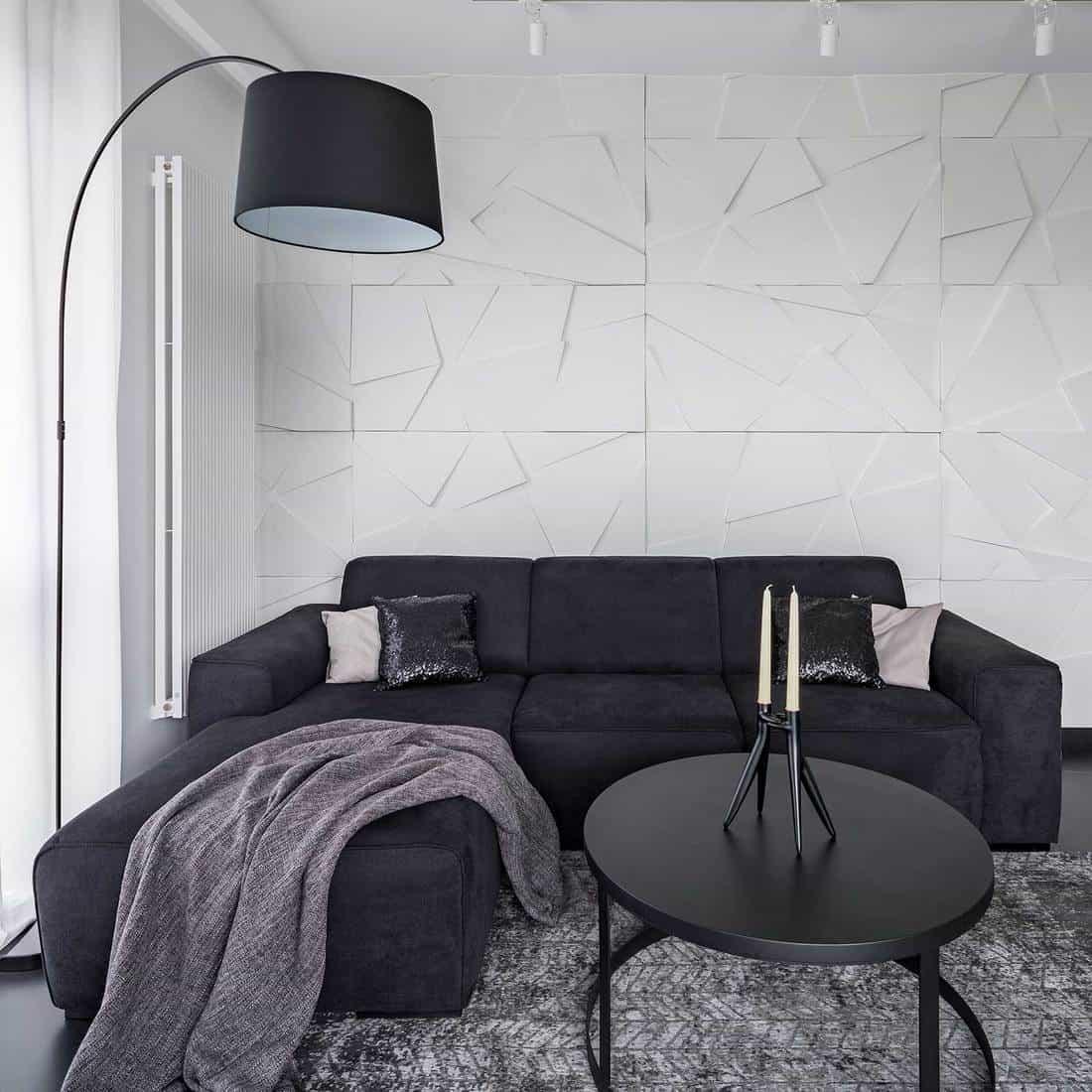 Black corner sofa, coffee table and arc floor lamp in modern apartment