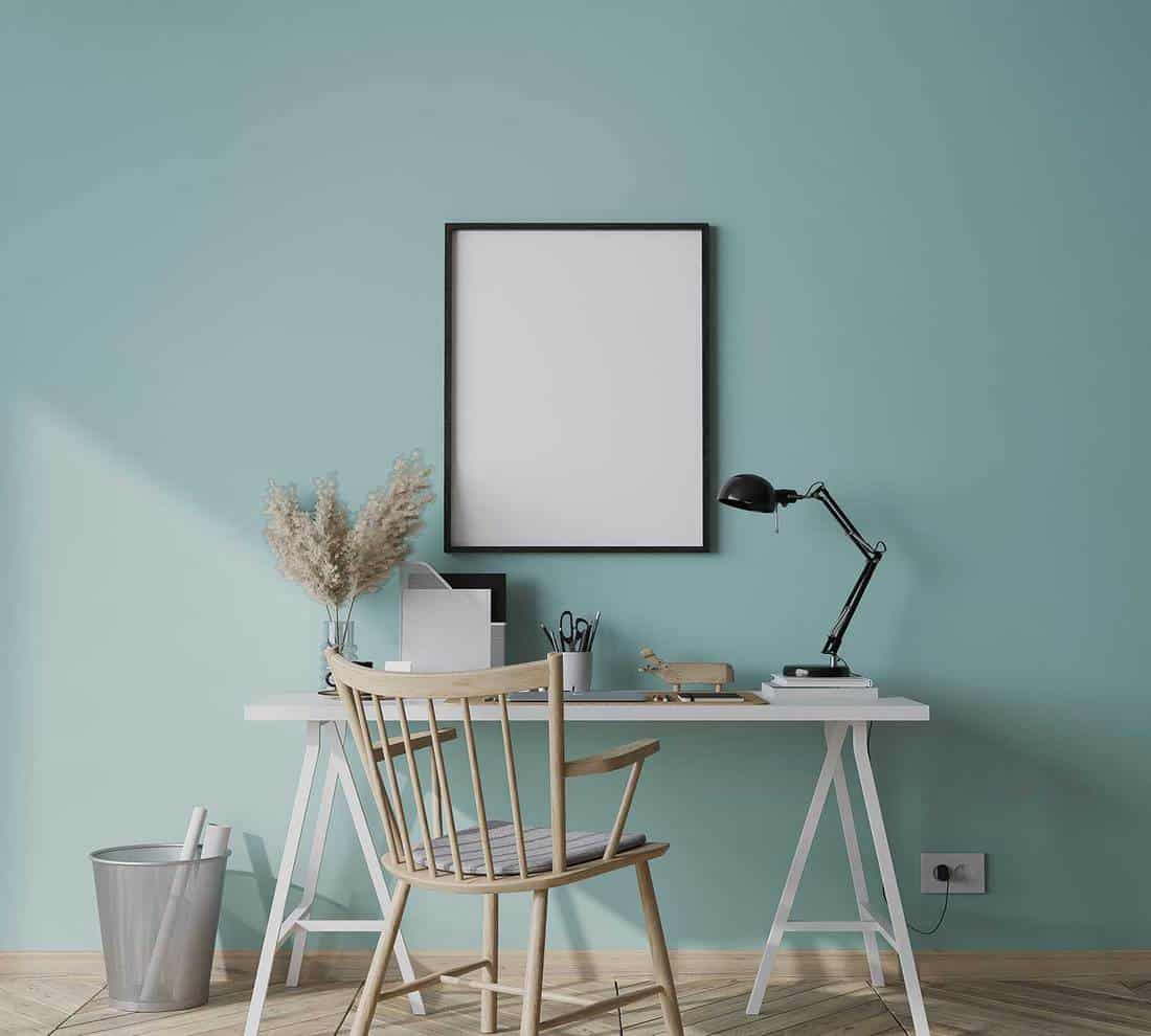 Black frame in bright farmhouse interior with white wooden office on blue wall