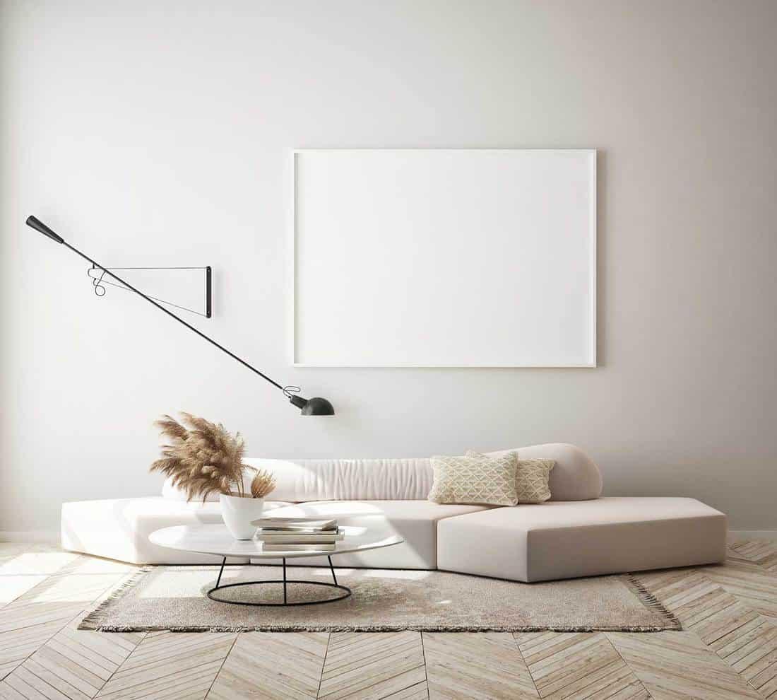 Blank white poster frame in modern Scandinavian living room with cozy sofa and carpet on hardwood floor