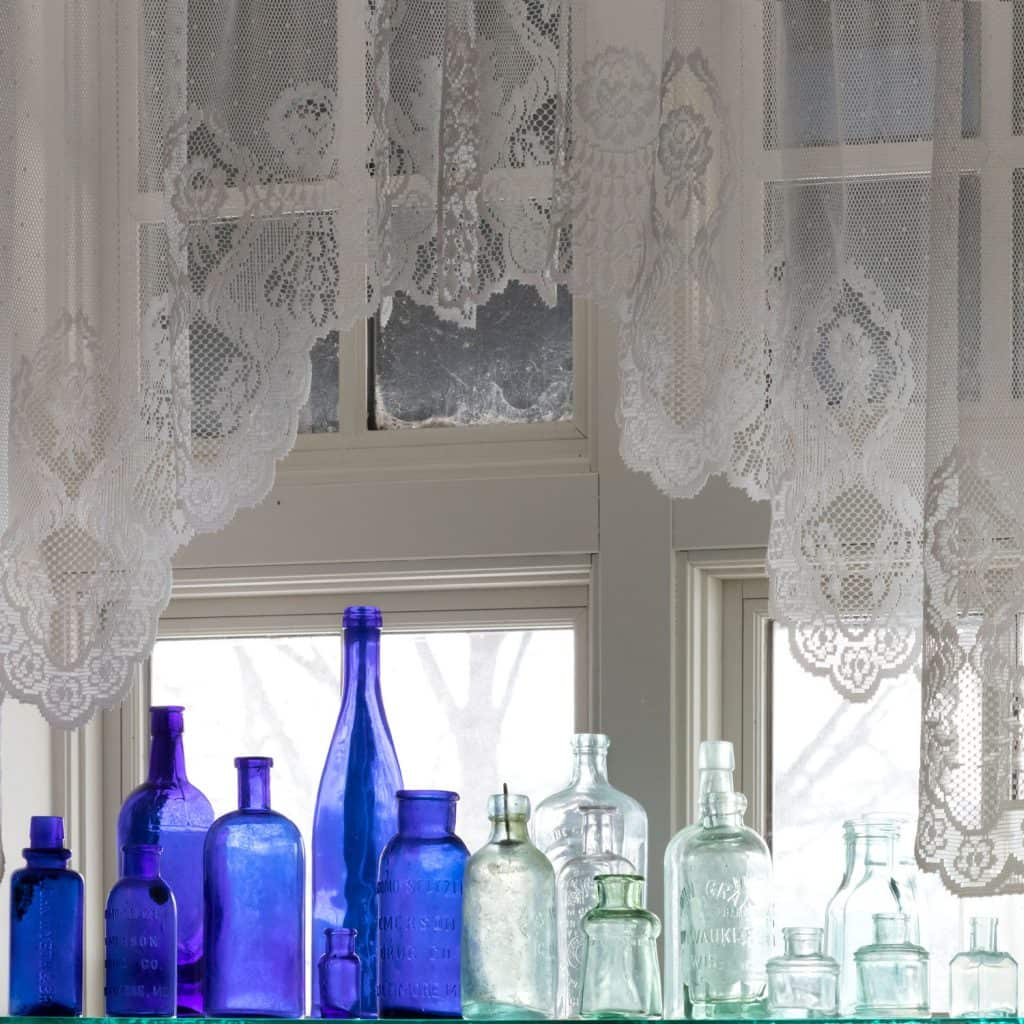 Blue and white empty liquor bottles placed on a windowsill