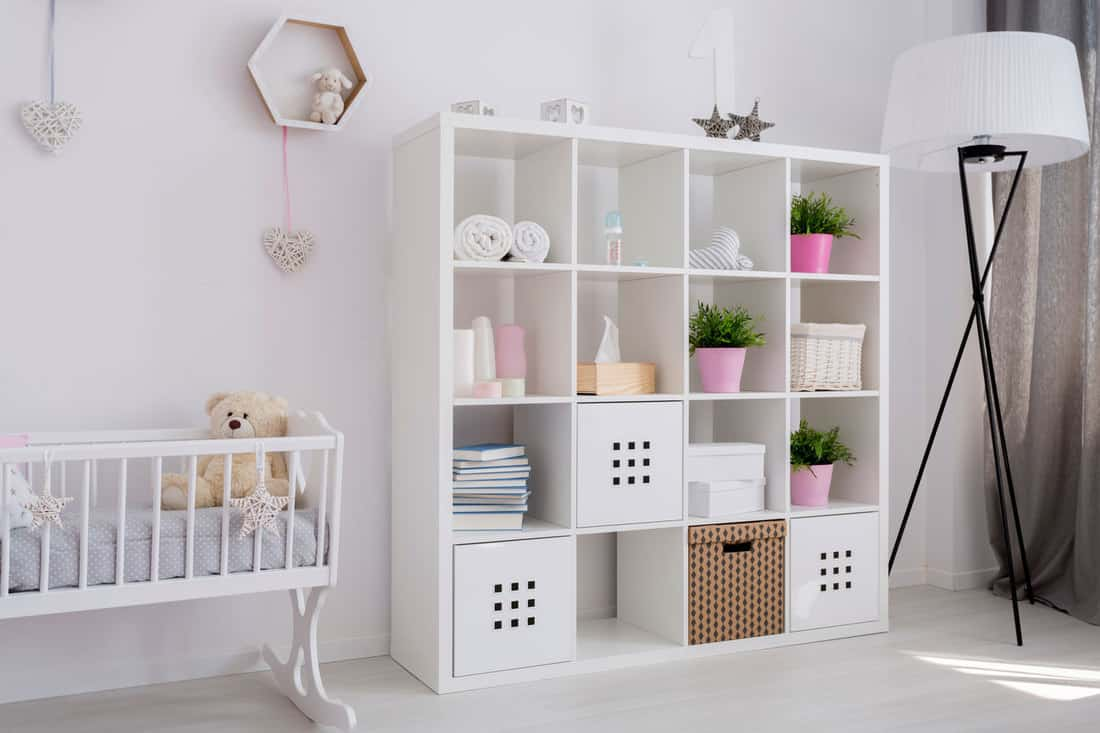 Bright baby girl room with white book case, baby cradle with a teddy bear and a lamp