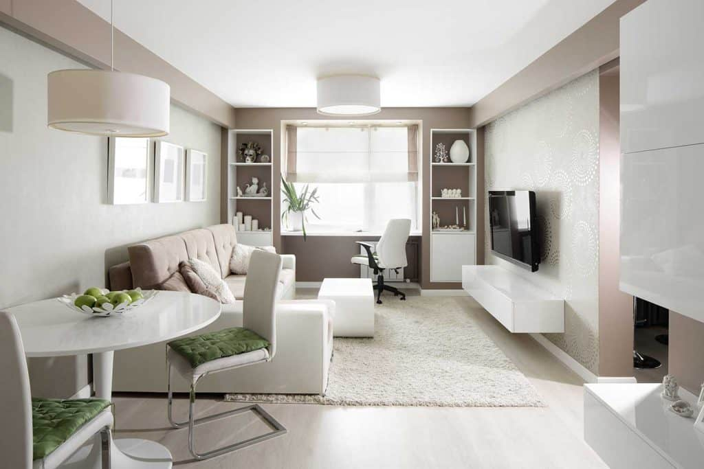 Bright interior of living room with corner sofa and carpet rug on floor