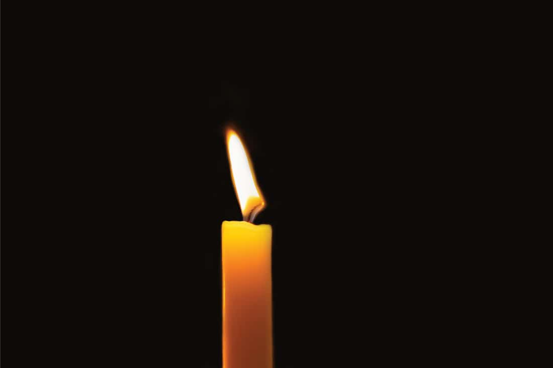 Burning wax candle in black background