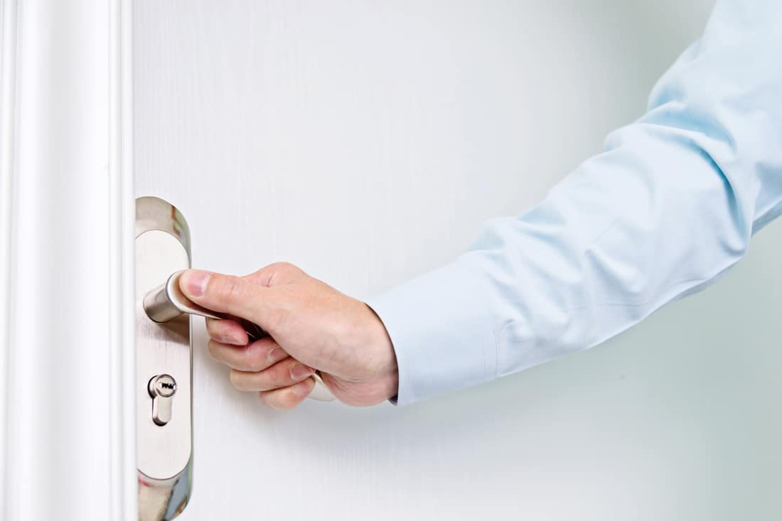 Businessman's hand opening a white door from the garage