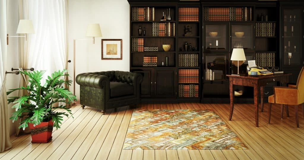 classical home interior (home library) with stylish furniture such as massive bookshelf, home office desk with typewriter and a very comfortable (perfect for reading a good book) Chesterfield armchair