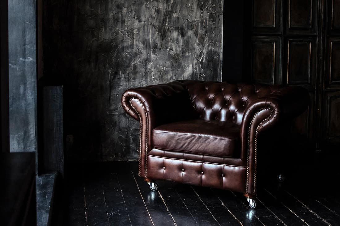Chesterfield Sofa of brown leather standing in center on concrete floor against dark grey wall with copy space, What Goes With A Chesterfield Sofa?