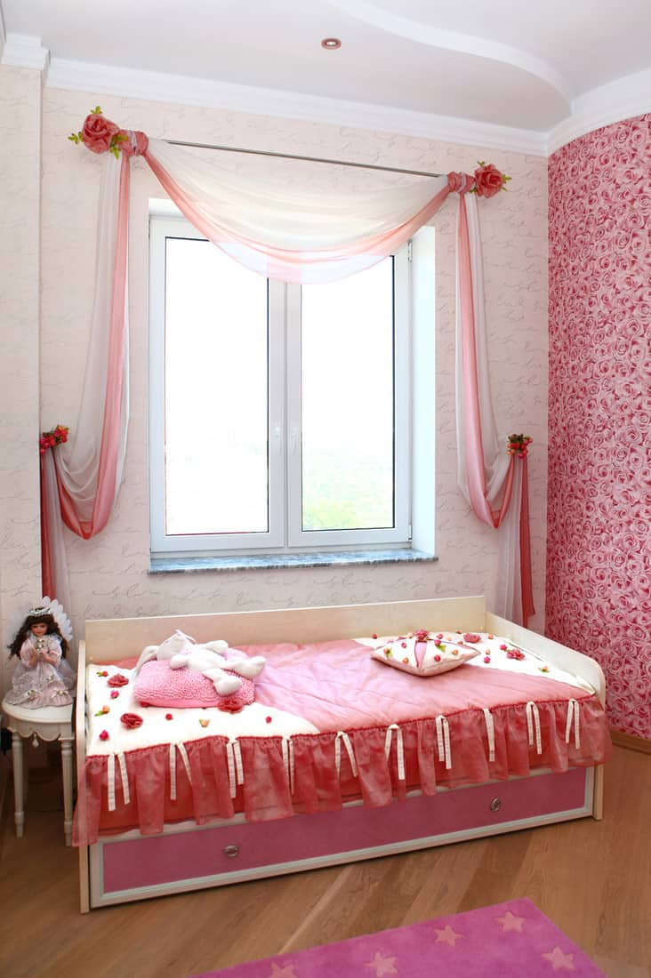 Children's bedroom with pink curtains covering a small window