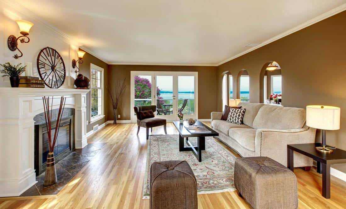 Classic brown living room with white fireplace, sofa and ottoman