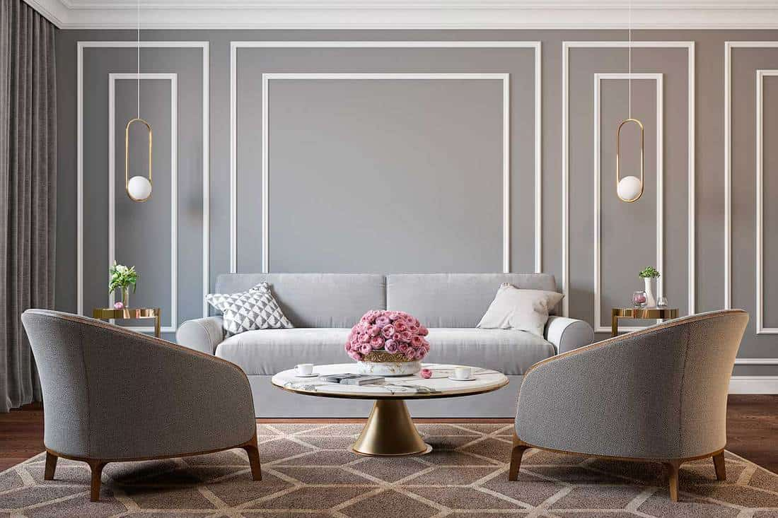 Classic gray interior with armchairs, sofa, coffee table, lamps, flowers and wall moldings