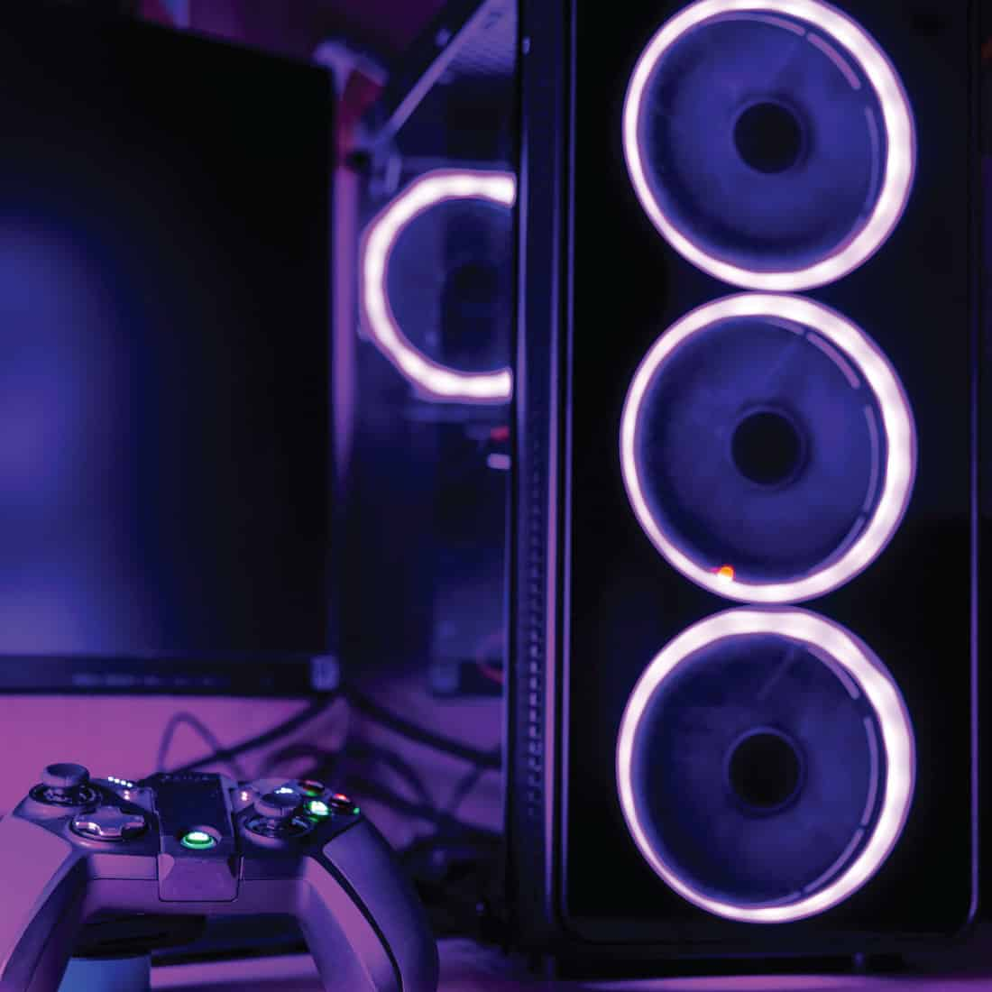 Close up of a gaming PC case and game pad with pink lighting