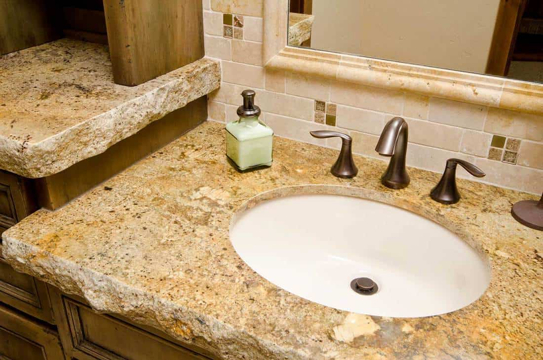 Close up of the bathroom sink with stone counter