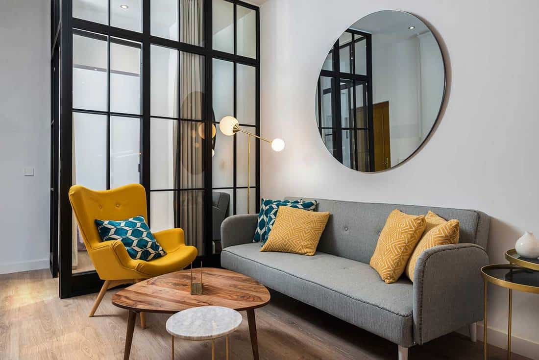 Colorful and cozy living room with a designer armchair and sofa along with a round decorative mirror and glass wall