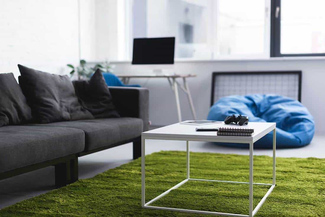 Computer on office table, black sofa, green carpet rug and coffee table in living room interior